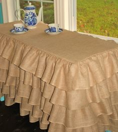 Ruffled tablecloth, could be put over cheap table and used has changing table in baby girls room