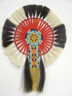 Native American Made Horsehair Bustle - This Native American Made Horsehair Bustle was created with white and black horsehair tied with red yarn. This piece is approximately 18 inches in diameter and designed for display. Some dancer have adapted them for actual use by adding a dance place and heavy straps. The beaded rosette and tail are all done by hand. Beading patterns and colors will vary. This is a spectacular piece.  $374.95