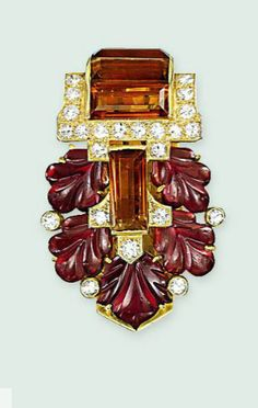 AN ART DECO GARNET, CITRINE AND DIAMOND CLIP BROOCH, BY CARTIER  The carved garnet plaque of foliate design, centring upon a baguette-cut citrine to the similarly-set citrine line with circular-cut diamond collet detail, circa 1930, 3.5cm high Signed Cartier London, no. 5612
