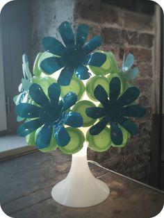 Abat-jour agrémenté de bouchons de bouteilles de lait et de pots de Danette découpés en forme de fleurs. Isabelle Kessedjian