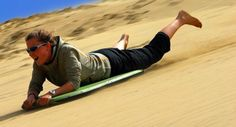 Go sandboarding at Te Paki Stream! Feel the thrill of riding down huge sand dunes in the North.
