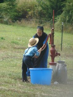 Amish working together to pump water
