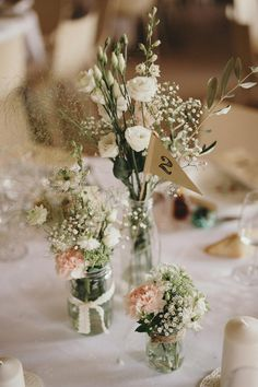 Bouquets de fleurs dans de simples bocaux et fanion en kraft pour le numéro de table