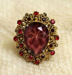 "Vintage Florenza Teardrop Ruby Red Rhinestone Adjustable Ring is set with a large teardrop stone encircled by ruby red rhinestones set in a filigree setting.    Excellent condition, measures 1 1/4"" ta"