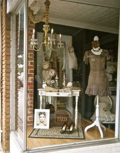 """Simple window: One showpiece people will give your WOM about (""""the shop with the chandelier""""), one dress form (easier than a mannequin) and one mood-setting piece of furniture as a riser. Notice, too, the area rug grounding all together. For more on displays for yr consignment, resale, thrift: The Big Book of Window Displays Especially for Resale at http://tgtbt.com/shopbuild.htm#2"""