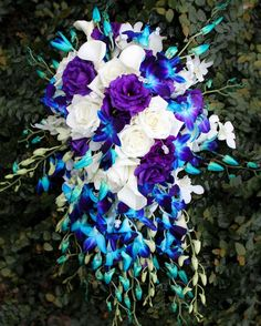 Kati's bridal bouquet was bold and bright in a classic cascade style!  #thefloralcottageflorist #bridalbouquet #cascadebouquet #bluedendrobium #louisianawedding #nolawedding #nolabride #neworleanswedding #neworleansbride