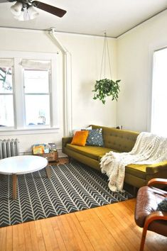 big olive sofa; black and white geometric rug; hanging plant; lovely living room