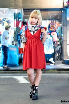 Akari is an 18-year-old student with dip dye bob hair. Her look features a red dress from Nadia Harajuku over a resale graphic t-shirt from the Tokyo resale shop Flamingo, worn with Tokyo Bopper platform shoes and sheer socks. Accessories: an on-off switch necklace she bought in Shimokitazawa and a Vivienne Westwood star backpack. Akari's favorite brands include Creephype and Arukara.