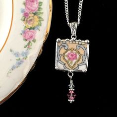 Dishfunctional Designs The original contemporary jewelry handcrafted from broken vintage china...  Artist made broken china jewelry necklace pendant with chain. Handcrafted from: Antique pink cabbage rose china with Swarovski crystals beaded drop.  Unique square pendant handcrafted from vintage china. Pendant measures approx. 7/8 by 2 & 1/4 including sterling silver bail and hand-beaded drop; silver bead with genuine Swarovski crystal beads.  18 chain included. Arrives gift boxed.  All of my…