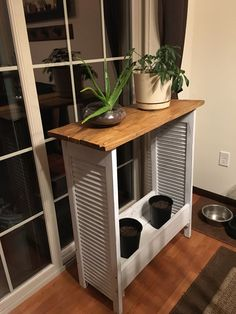 Repurposed shutters and pallet wood into a plant shelf/table.