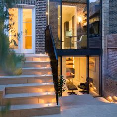 Double height glass extension to Grade II* listed building in Kensington using minimal windows sliding doors to both floors with a frameless balustrade to create a Juliette balcony on first floor