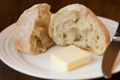 Shot of one Unbelievably Easy Artisan Roll broken open on a white plate with a knife and a pat of butter