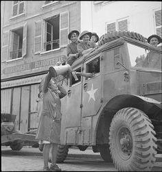 Le 27 août 1944, une habitante de Vernon offre à boire à un équipage d'artilleurs. Le véhicule semble être un tracteur d'artillerie Morris C8 qui remorque un canon anti-char Ordonance QF 17 pounder.
