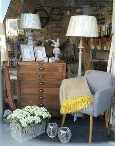 Window display in Wadebridge.   Grey occasional chair, yellow and grey wool blanket, architect drawers, wood floor lamp, artificial hydrangea, reclaimed coat hooks.