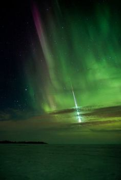 Meteor falling through the Aurora Borealis
