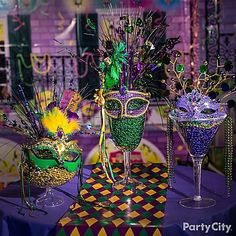 """Centerpiece + grab-and-go Mardi Gras accessories = these easy to make decorations! Everyone will be jazzed over these giant cocktail glasses filled with tons of """"throws"""" and adorned with feathered masks!"""