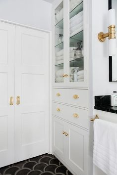 Amazing bathroom features a built-in glass front linen cabinet placed atop drawers and cabinets adorned with polished brass cup pulls and knobs atop a black fan shaped cement floor, Arto Conche Tiles, next to a closet finished with pocket doors and brass hardware.
