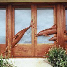 Entry doors with hand-carved dolphins in heavy relief. Solid teak with etched glass. More at www.davidfrisk.com