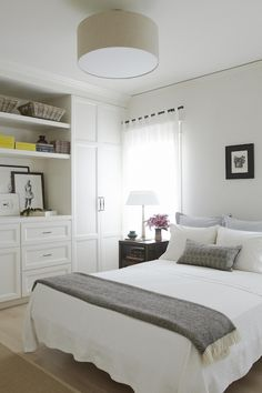 Lovely bedroom with white ceiling height built-in closets and drawers with open display
