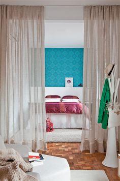 """Numa ponta, a cama. Na outra, o closet. Entre as duas extremidades do ambiente, 7 m de distância. Esse formato comprido desagradava à moradora, mas uma cortina com função de divisória resolveu o problema. """"Se tivesse optado por uma porta de correr, os espaços ficariam compartimentados. O tecido trouxe fluidez"""". Um trilho suíço, fixado no teto, sustenta a cortina de gaze de linho, que divide com leveza os espaços de dormir e vestir."""