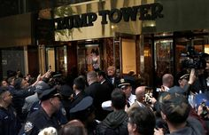 Trump waves to supporters outside the front door of the infamous Trump Tower where he lives in Manhattan on October 8.