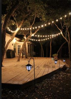 Outdoor patio deck with string lights illuminating the home, trees and deck.
