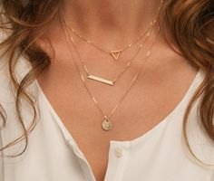 3 Layering Necklaces: a Small Skinny Bar Necklace, a Floating Triangle Necklace and a Small Disc Necklace. Comes in Sterling Silver or 14k Gold