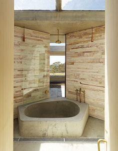 A material palette of raw concrete, Mudgee stacked stone and brass fittings is sympathetic to place.