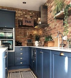 Open brick work in the kitchen works so well alongside the dark blue kitchen units and the white countertops.