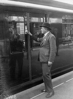 A passenger opening one of the doors on the Hammersmith and City Underground Line, which have been fitted with new buttons for opening and closing doors, 1936.