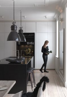Modern kitchen from Multiform with white cabinets, black kitchen island and industrial pendants.