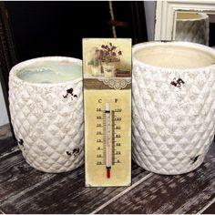 Metalowy termometr w kremowym kolorze, u góry wzór kwiatów w iście prowansalskim stylu.