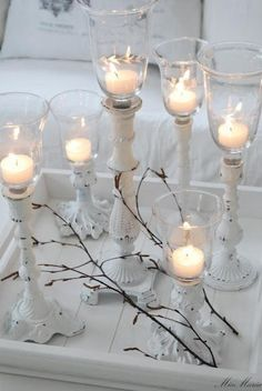 Gorgeous white votive candles on white painted iron pillars with bare Christmas branches -- stunningly simple and rustic holiday table decoration style idea. So wintry and cozy!