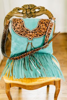 "This one of a kind hand tooled purse will be a sure to turn heads! Made from a tiffany blue distressed leather this bag features vintage inspired floral tooling, a lined interior with one pocket, a fully tooled adjustable strap and 14"" of fringe! Height: 13""Width: 15"""