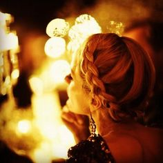 beautiful braids in her hair. The hairdo is amazing especially with the pretty night lights