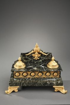 A rectangular green marble and gilt bronze inkstand composed of two inkwells hemmed with fluted frieze and crosspiece with their lids chiselled with foliages and pine cone atop, and a...