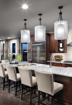 When it comes to lighting your kitchen - don't be afraid to make a statement with oversized pendants above the island. Progress Lighting Invite lights enhance this welcoming, open concept kitchen.