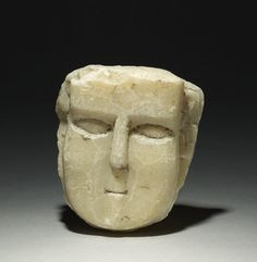 sculpture; Ancient South Arabian; 3rdC BC-3rdC; Yemen; Yemen. Crudely carved calcite-alabaster human face in relief? with angular features and incised eye; top of head from hair line and back of object are flat.