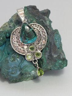 """Dramatic handmade and polished cabachon Chrysicolla pendant accented with 4 faceted Peridot gemstones, set in 925-hallmarked sterling silver. Largest vertical dimension from bail to dangle: 2"""""""