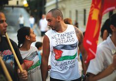 PEOPLE TAKE part in a protest against Israel in Malaga, Spain, on August 8. The words on the shirt read 'Netanyahu must be judged. Second Zionist-Nazi Holocaust.' Photo By: REUTERS