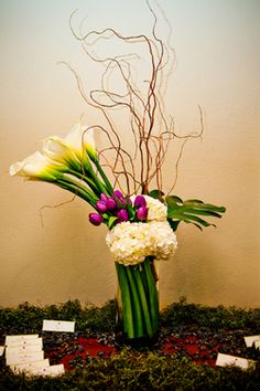 Purple tulips, white calla lilies ,white hydrangea, curly willow and monestera leaves in a clear cylinder vase