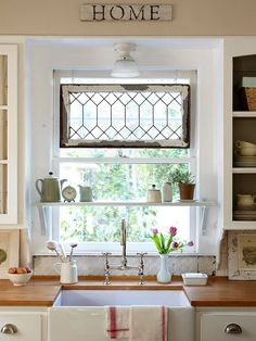 Window shelf!  This kitchen has all the things that I love in it:  pressed tin (I would love to have that as ceiling tile or a back splash), a farmhouse sink, salvaged leaded-glass windows used as art, cup-style drawer pulls, the color red, white cabinets, baskets....oh, my!!