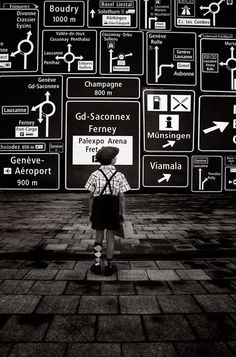 ♂ Black & white boy standing at the front of a wall of signage.
