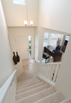 Entrance to the Soho showhome in EvansRidge; white walls, light carpet and hardwood floors with dark accessories and furniture to contrast