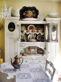Yellow walls, and white china cabinet.