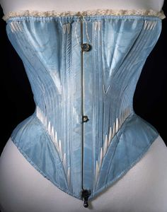 Corset (front view), blue silk stiffened with whalebone, possibly English or French, 1864.    http://www.vam.ac.uk/content/articles/c/crinolines-crinolettes-bustles-corsets-1860-1880/