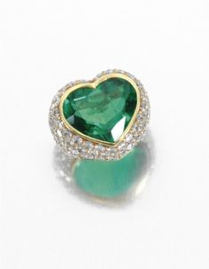 JEWELS FROM THE COLLECTION OF LILY MARINHO - Emerald and diamond ring -  Centring on a heart-shaped emerald, the yellow gold mountpavé-set with brilliant-cut diamonds, signed Natan.