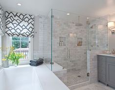 master bathroom with custom roman shades in F Schumacher Zimba Charcoal Fabric, cool gray paint color, drop-in tub, seamless glass shower with marble subway tiles shower surround with rain shower head and charcoal gray bathroom vanity.: