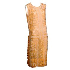 Cotton dress in a flattering shade of peach, profusely decorated with small white glass beads and larger tan wooden beads. There are undulating bands of beads, circles and teardrops, all bordered by linear bands of beadwork | France, 1920's