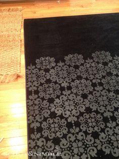 Stencil a plain rug with paint.
